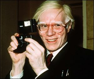 Pop artist Andy Warhol smiles in this 1976 photo.