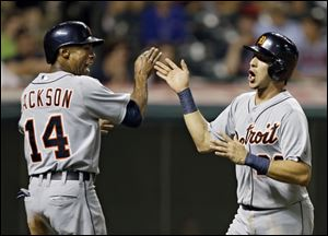Detroit Tigers' Austin Jackson (14) and Hernan Perez celebrate after scoring on a double by Prince Fielder in the 14th inning.