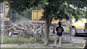 An FBI agent watches as the house where three women were held captive and raped for more than a decade is demolished in Cleveland today.