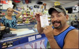 Tony Valdez, right, shows off his Powerball lottery ticket he purchased from Vanessa Sanchez, left, Wednesday in San Antonio.