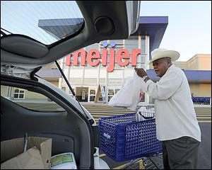 Lee Greenwood of Southfield, Mich., loads his car after shopping at the Meijer that recently opened in Detroit. The chain is boosting its staff in response to growth and the looming holiday season.