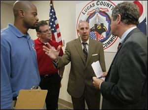 Lucas County Veterans Service officer Rick Glover, left, and Lee Armstrong, executive director of the Lucas County Veterans Service Commission, listen as Patrick Grames of Oregon explains the barriers he has faced in his VA claim to Sherrod Brown, right.