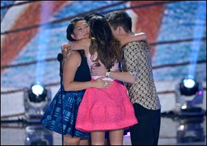 The cast of 'Glee,' from left, Jenna Ushkowitz, Lea Michele, and Kevin McHale hug on stage at the Teen Choice Awards at the Gibson Amphitheater on Sunday in Los Angeles.