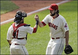 Indians catcher Carlos Santana, left, and closer Chris Perez celebrate after the final out in a 6-5 win against the Los Angeles Angels on Sunday in Cleveland.