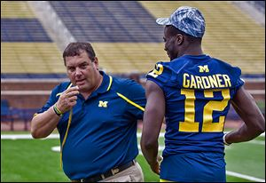 Michigan coach Brady Hoke jokes with quarterback Devin Gardner at the team's media day on Sunday.