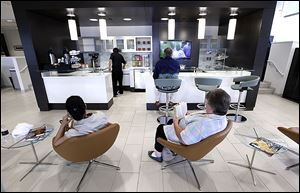 Customers sit in the cafe area of Hines Park Lincoln in Plymouth, Mich., the result of Ford Motor Co.'s dealer makeovers to appeal to younger, more discerning buyers for its Lincoln line of cars. Ford purged underperforming dealerships and is prodding the rest to make expensive updates.