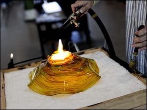 Master Instructor of Glass Leonard Marty polishes the bottom of a piece using a blow-torch.
