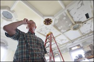 German native Hans Klinck, 65, of Findlay inspects the plaster repairs he made on the original ceiling in Courtroom 1 on the third floor of the Hancock County Courthouse.