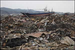 In this March, 2011 photo, a beached ship sits among the rubble in a residential neighborhood after the March 11 earthquake and tsunami in Kesennuma in Miyagi prefecture, northern Japan. The stranded fishing boat that became a symbol of the devastation of Japan's 2011 tsunami has long divided a northeastern coastal city.