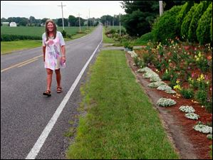 Cheryl Metro walks down Co. Rd. 8-1 along her roadside garden in Delta.