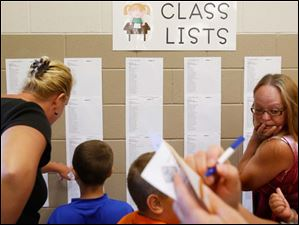 Heather Boose, right, turns to talk to her daughter Jasmine, 7, while other students and parents take a look at their class listings.