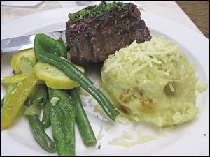 A grilled filet with Bernaise sauce served with mashed potatoes and mixed vegetables.