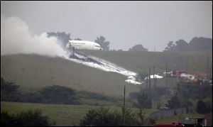 Debris burns as a UPS cargo plane lies on a hill at Birmingham-Shuttlesworth International Airport after crashing on approach today.