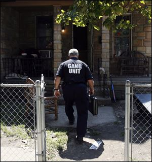 Doug Allen of the Toledo Police gang unit enters a home.