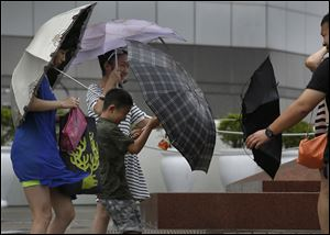 Tourists battle against strong wind near the waterfront in Hong Kong today as Typhoon Utor lashes Hong Kong with wind and rain.