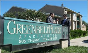 Jack Ford, left, talks with Joe McNamara, city council member and mayoral candidate, in front of the troubled Greenbelt Place Apartments on Wednesday.