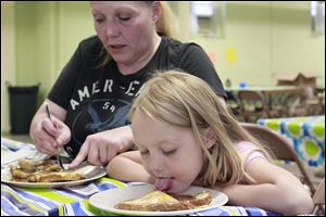 Natalie Fisher helps her daughter, Savannah Scott, 7, eat French toast at Baby University, a series of parenting classes for low-income parents at the South Toledo Community Center.