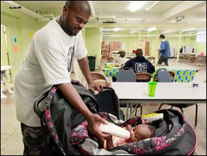 Randall Patterson feeds his daughter  Randi, 3 months, a bottle in her pram. Mr. Patterson graduated from 'Baby University.'