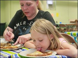 Natalie Fisher, left, eats french toast with her daughter Savannah Scott, 7. Ms. Fisher is a graduate of 'Baby University.'