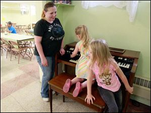 Natalie Fisher, left, watches as her daughters Shaylah Scott, center, 3, and Savannah Scott, 7, right, play on the piano at the South Toledo Community Center.