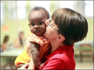 Cyndra Nungester, manager of Western Avenue Ministries which houses Baby University, gives baby Randi Patterson a kiss.
