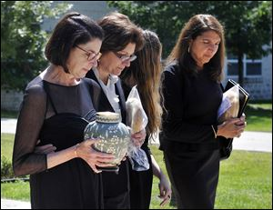 Terri DeLeon, a niece of Helen Thomas, carries the urn with the ashes of Mrs.Thomas along with family members after a memorial service for the pioneering journalist at St. George Antiochian Orthodox Church in Troy, Mich.