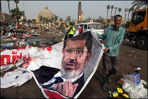An Egyptian pulls a banner of Egypt's ousted President Mohammed Morsi near debris left at a protest camp in Nahda Square, Giza, Cairo, Egypt today.