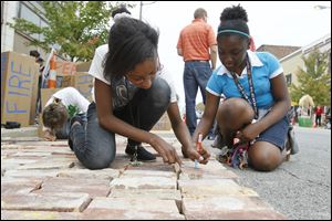 Toledo School for the Arts seventh-graders Ayiana Byrd, left, and Jayla Aimuanvbosa, right, sign their names to bricks at the Toledo Warehouse Association space.