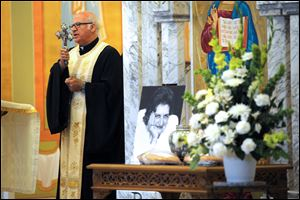 The Rev. George Shalhoub offers a blessing during a memorial service for pioneering journalist Helen Thomas at St. George Antiochian Orthodox Church in Troy, Mich. Mrs. Thomas, 92, died last month in Washington.