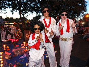 Nicholas Woodlief, 7, left, his sister Annabelle Woodlief, 11, and friend, Eli Crain, 11, right, strike an Elvis Presley pose at Graceland, Presley's home, before the annual candlelight vigil Thursday in Memphis, Tenn.