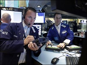 Trader Jonathan Corpina, left, and specialist Michael McDonnell work on the floor of the New York Stock Exchange today.