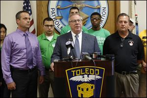 D. Michael Collins, independent candidate for Toledo mayor, center, is endorsed by  Dan Wagner, president of the Toledo Police Patrolman's Association, left, and Capt. Jeffrey A. Romstadt, president of Toledo Firefighters Local 92,  right, during a news conference at the Toledo Police Patrolman's Union Hall.