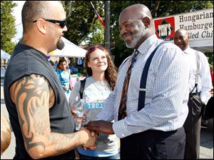 Toledo Mayor Mike Bell talks with Louis and Patricia Acevedo while campaigning.