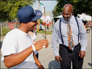 Toledo Mayor Mike Bell jokes with Rico Howard while campaigning Saturday at the Birmingham Ethnic Festival in Toledo.