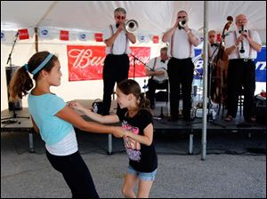 Left Olivia Swartz, 9, and Liliana Thompson, 9, dance as the Cake Walkin' Jass Band performs.