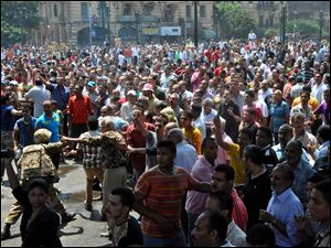A member of Egyptian security forces, at left, tries to keep crowds away from the al-Fatah mosque, in Ramses Square, downtown Cairo.