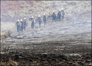A team of hotshots walk along a fire line near homes on Croy Road and the Rotorun ski hill west of Hailey Idaho today.