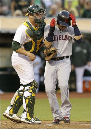 Cleveland Indians' Nick Swisher, right, scores past Oakland Athletics catcher Stephen Vogt in the third inning.