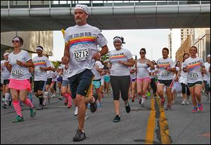 Runners head up Summit Street from Promenade Park during the Color Run on Saturday on the streets of downtown Toledo.