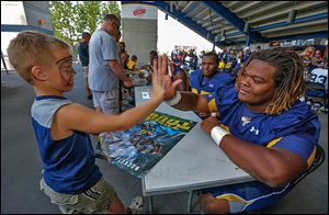 Kyler Koopmans, 5, of Toledo, high-fives UT defensive lineman Marquise Moore after getting an autograph during Fan Appreciation Day at the Glass Bowl.