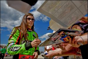 Danica Patrick signs autographs for fans before taking her qualifying lap for the NASCAR Sprint Cup Series at Michigan International Speedway. She will start 28th in today's Pure Michigan 400.