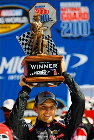 Driver James Buescher holds up the Michigan National Guard 200 trophy after winning Saturday at MIS.