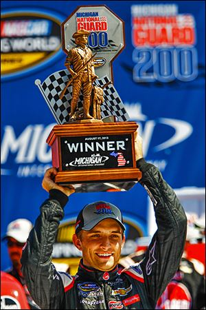 James Buescher celebrates his win in the NASCAR Camping World Truck Series Michigan National Guard 200.