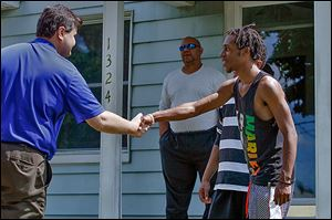 Joe McNamara, left, greets Donathan  Floyd, 18, on Potomac Drive In the background is Willie Howard.