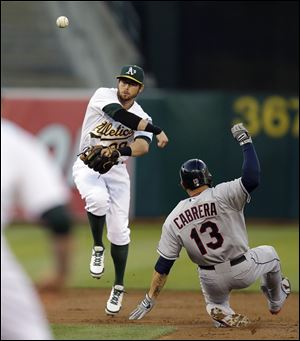 Oakland Athletics second baseman Eric Sogard, left, throws over Cleveland Indians' Asdrubal Cabrera to complete a double play in the second inning.