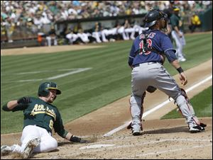 Oakland's Jed Lowrie, left, scores past Cleveland Indians catcher Yan Gomes after a single from Josh Donaldson during the second inning Sunday in Oakland, Calif.