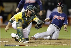 Cleveland Indians' Drew Stubbs, right, slides to score behind Oakland Athletics catcher Derek Norris in the ninth inning Saturday in Oakland, Calif.  Stubbs scored on a single by Nick Swisher.