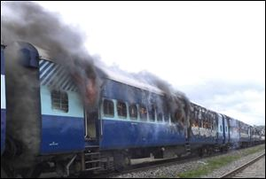 Coaches of the Rajya Rani Express train burn after a mob set it on fire as it ran over a group of Hindu pilgrims at a crowded station in Dhamara Ghat, Bihar state, India, today.