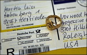 A gold aviator's ring that belonged to U.S. Army Air Corps 2nd Lt. David C. Cox during World War II rests on a freshly opened package from Germany.