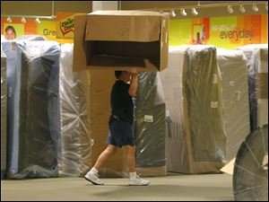 A worker carries a box as he and others work in the clearance center of the new Art Van furniture store.
